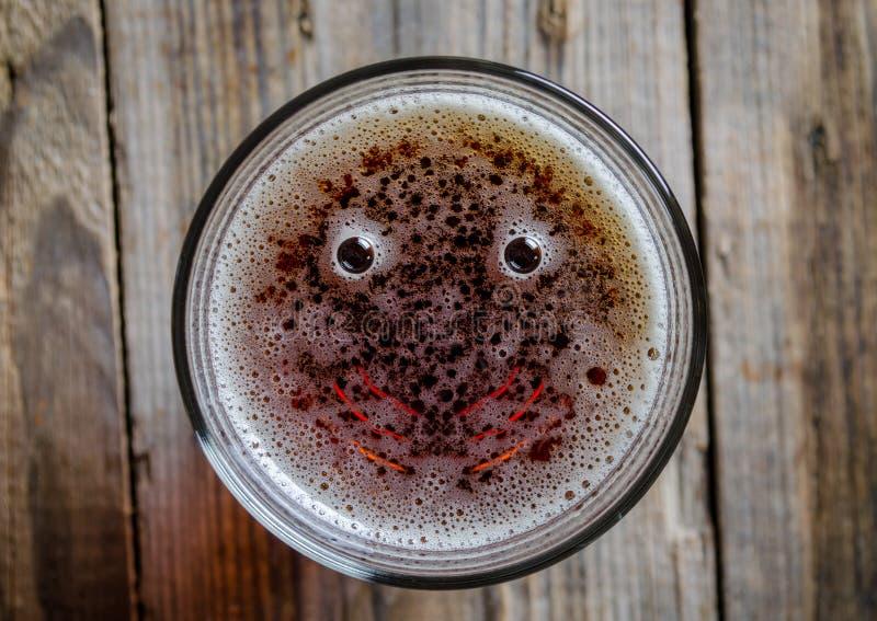 Exponeringsglas av öl med två bubbla och leende royaltyfri bild
