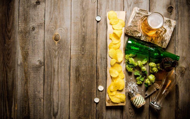 Exponeringsglas av öl och chiper på trätabellen fotografering för bildbyråer