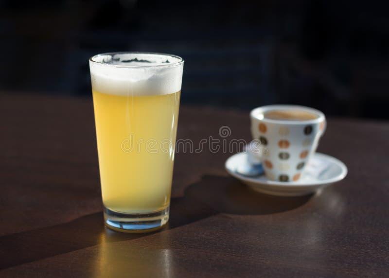 Exponeringsglas av öl och en kopp kaffe på kafétabellen arkivfoton