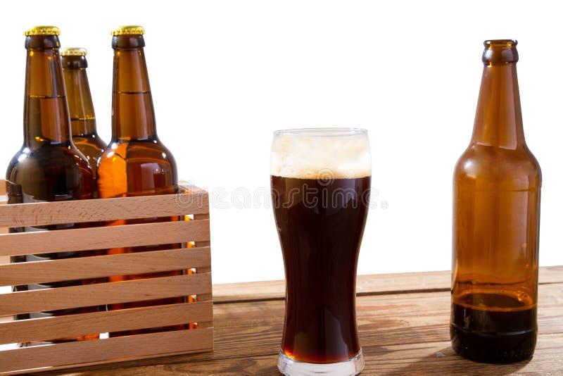 Exponeringsglas av öl och flaskor med ingen logo på trätabell isolerat kopieringsutrymme, glasflaska royaltyfri bild