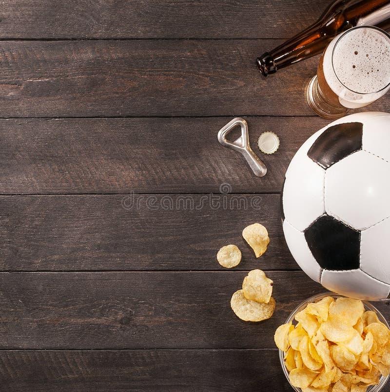 Exponeringsglas av öl och fotbollbollen träutrymme för text royaltyfri bild