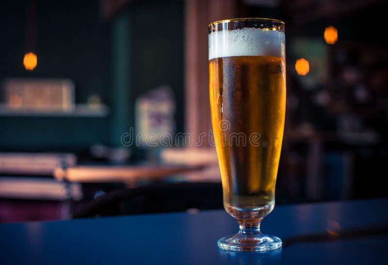 Exponeringsglas av öl på en wood tabell arkivfoto