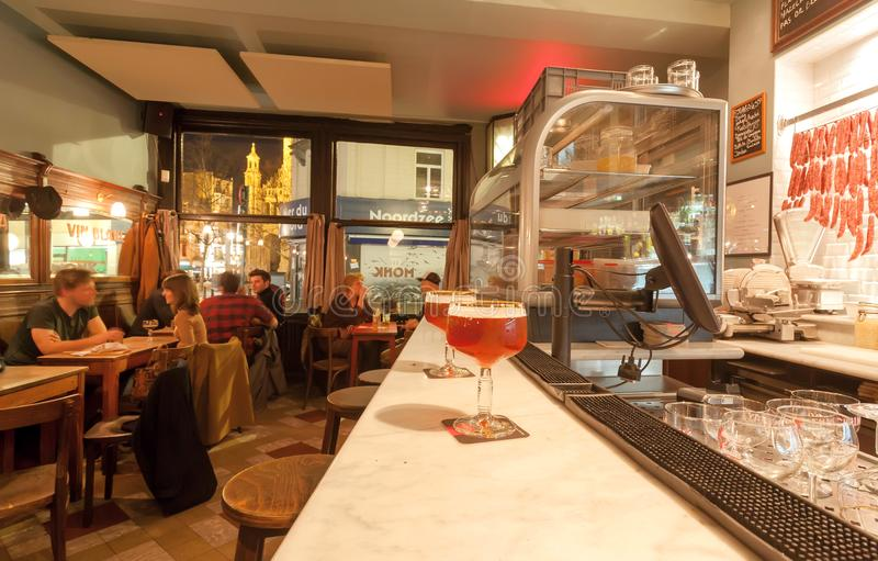 Exponeringsglas av öl på stångräknare av det eleganta retro kafét med att dricka folk som har lunch arkivbild