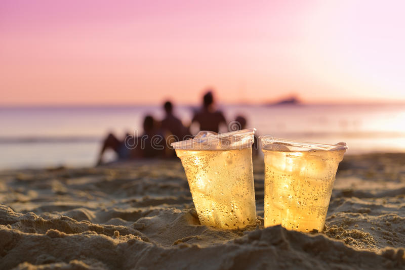 Exponeringsglas av öl på strandsand på solnedgången royaltyfria foton