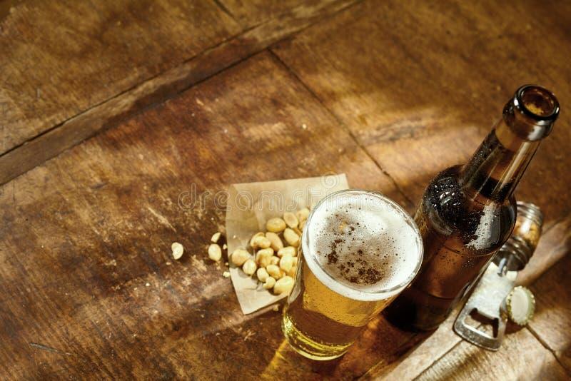Exponeringsglas av öl på tabellen med öppnaren och jordnötter arkivbild
