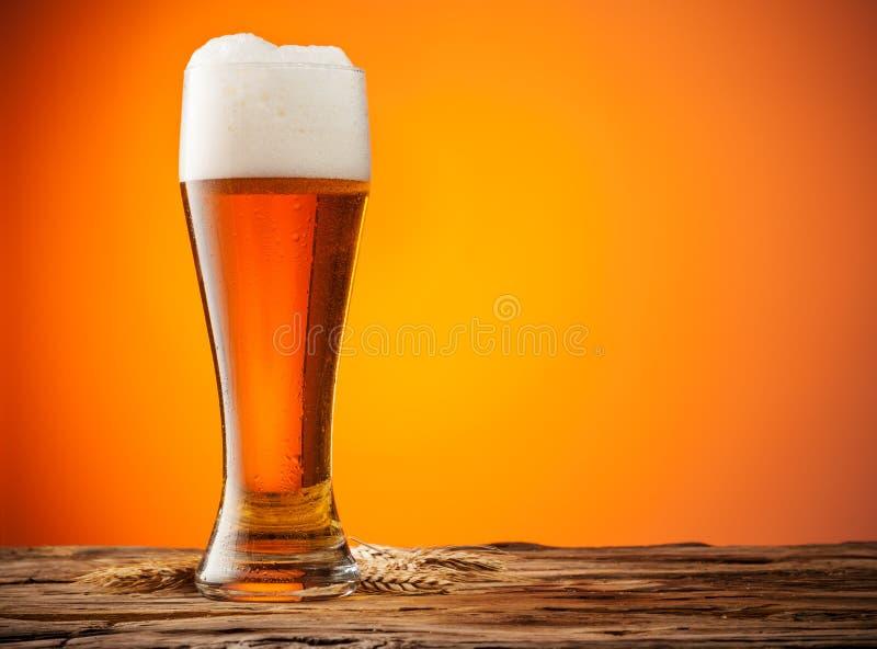Exponeringsglas av öl på trä med orange bakgrund royaltyfri fotografi