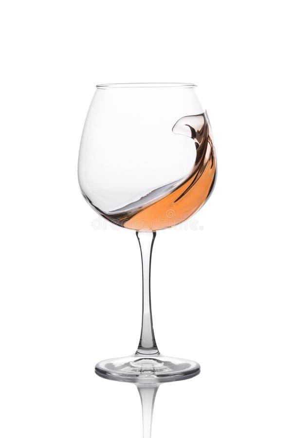 Exponeringsglas av bärnstensfärgat vin med färgstänk som isoleras på vit fotografering för bildbyråer