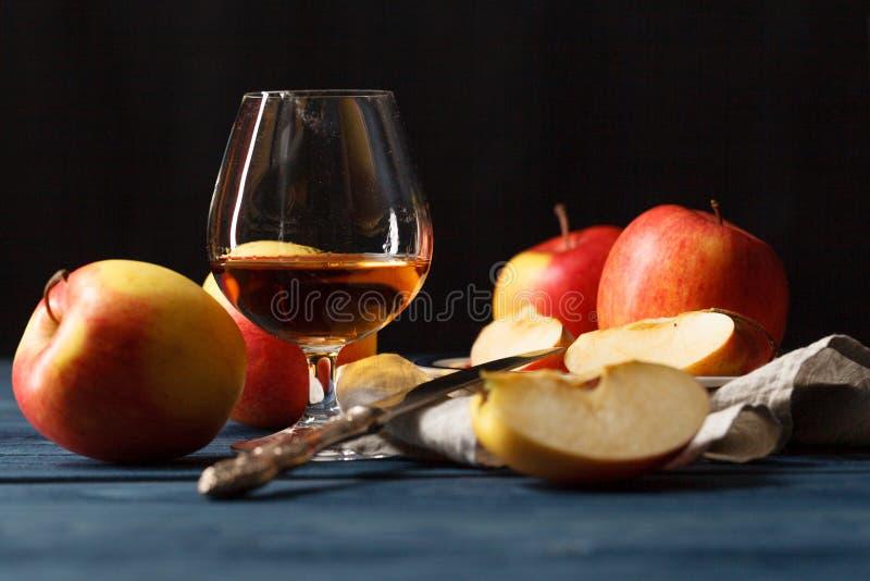 Exponeringsglas av Calvados konjak och röda äpplen royaltyfria foton