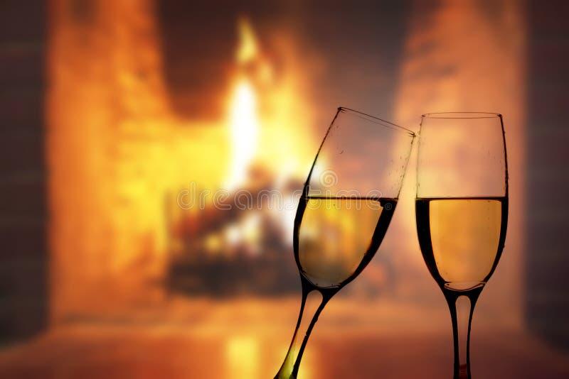 Exponeringsglas av champagne framme av den varma spisen arkivfoton