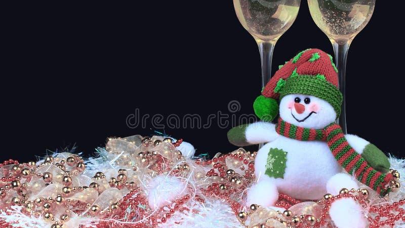 Exponeringsglas av champagne med snögubbear, dekorerad svart bakgrund arkivfoton