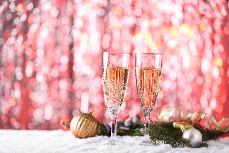 Exponeringsglas av champagne och juldekoren på snö mot suddiga ljus fotografering för bildbyråer
