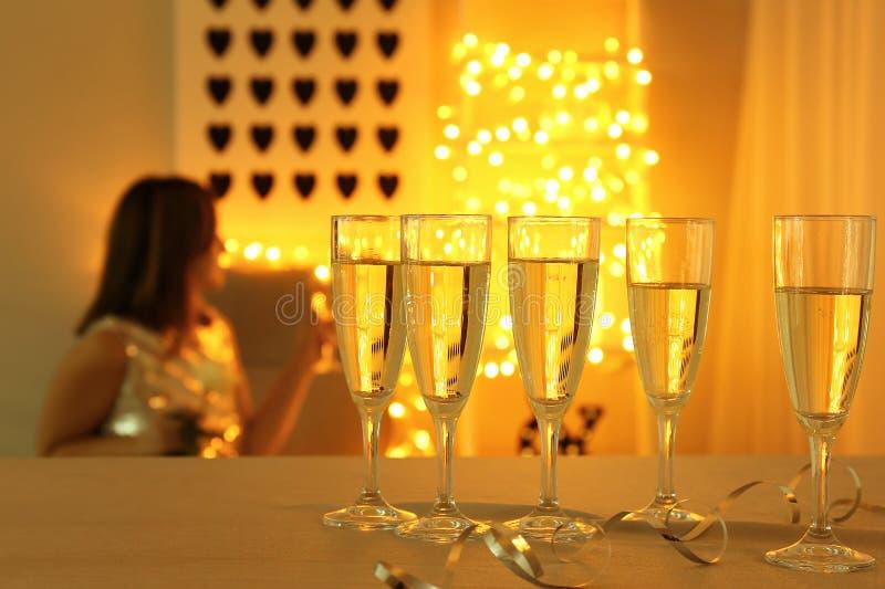 Exponeringsglas av champagne på den ljusa tabellen i rum arkivfoton