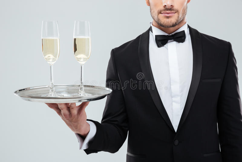 Exponeringsglas av champagne på magasinet holded vid uppassaren i smoking royaltyfri foto