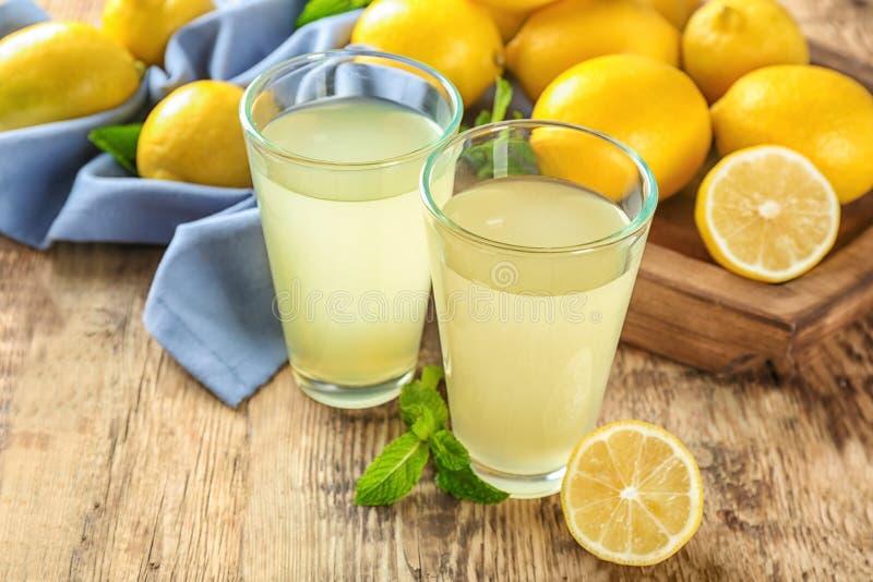 Exponeringsglas av citronjuice och nya citroner arkivfoton
