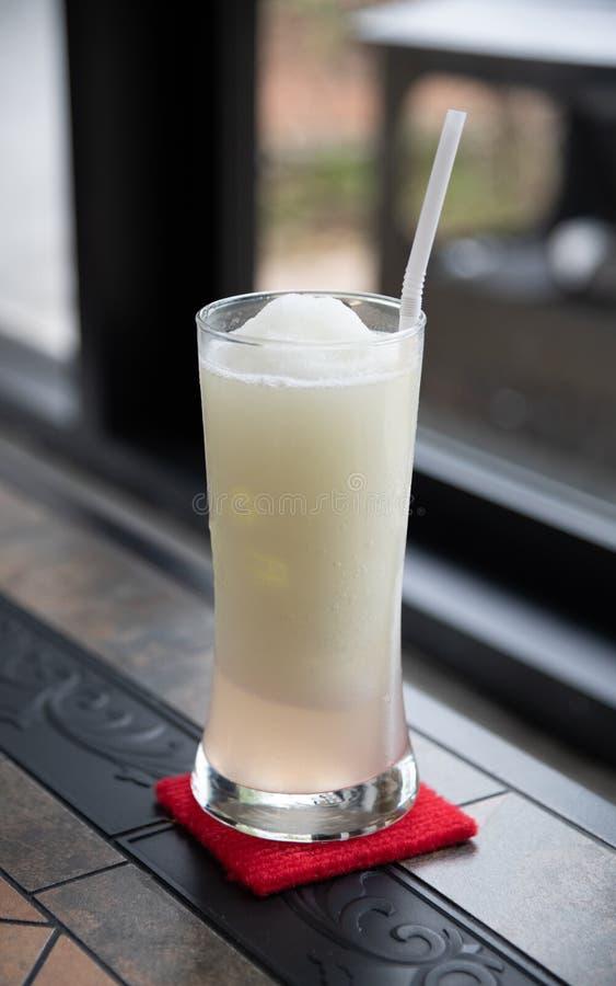 Exponeringsglas av citronjuice på den klassiska tabellen med fönsterljus royaltyfri fotografi
