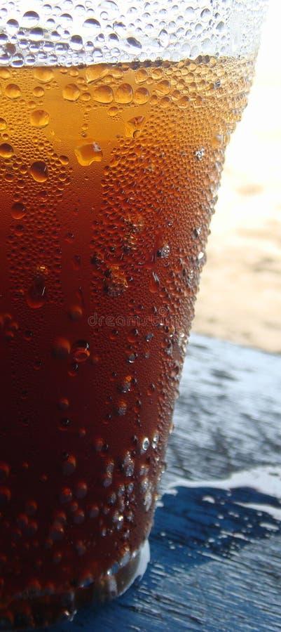 Exponeringsglas av cola på en blå trätabell på stranden med vattenkondensation tappar stekflott på sidan royaltyfri foto