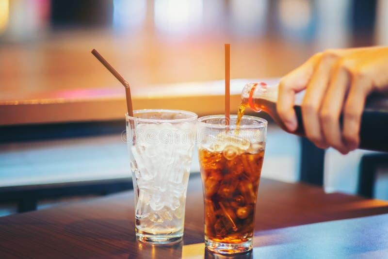 Exponeringsglas av cola som plaskar med is på trätabellbakgrund royaltyfri bild