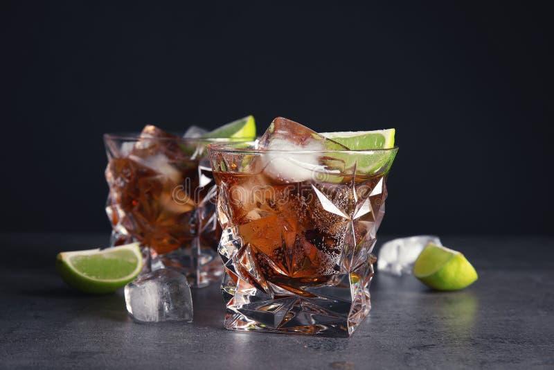 Exponeringsglas av den förnyande drinken med iskuber och limefrukt på tabellen royaltyfri fotografi