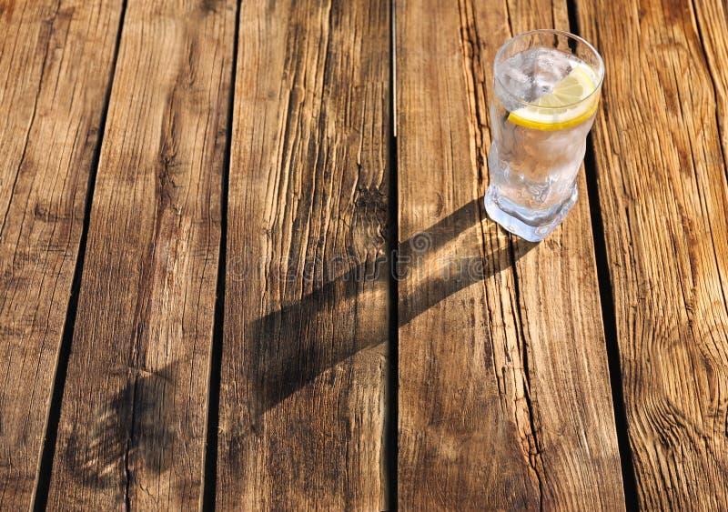 Exponeringsglas av den förnyande drinken med is och citronen för varm sommardag på trätabellen arkivfoton