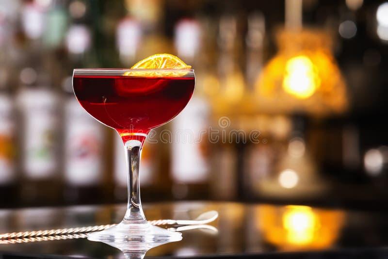 Exponeringsglas av den körsbärsröda färgalkoholcoctailen dekorerade med orange sli royaltyfri fotografi
