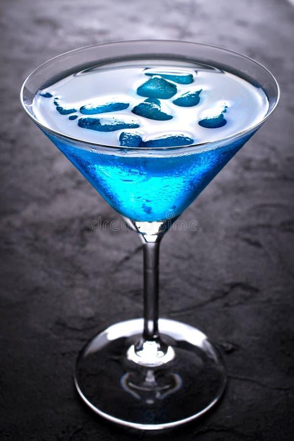 Exponeringsglas av den nya förkylningblåttcoctailen med iskuber på den mörka stångtabellen fotografering för bildbyråer