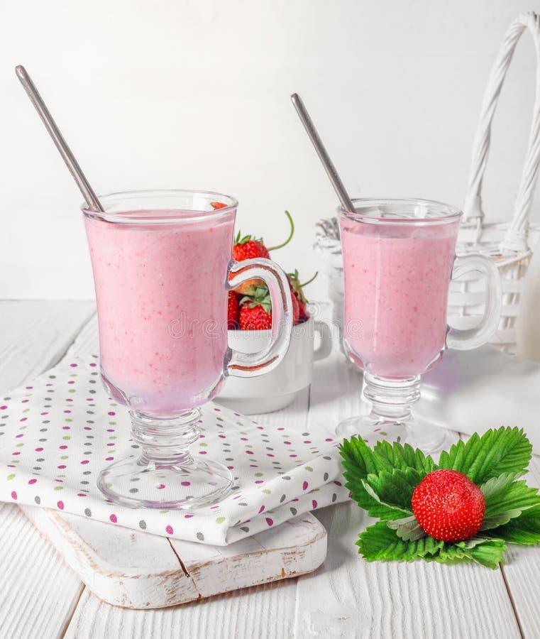 Exponeringsglas av den nya jordgubben och yoghurtsmoothien p? den vita tr?tabellen arkivbild