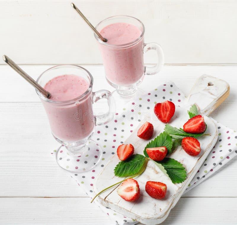 Exponeringsglas av den nya jordgubben och yoghurtsmoothien p? den vita tr?tabellen arkivfoton