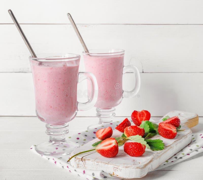 Exponeringsglas av den nya jordgubben och yoghurtsmoothien p? den vita tr?tabellen fotografering för bildbyråer