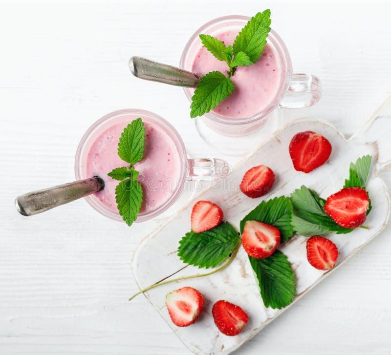 Exponeringsglas av den nya jordgubben och yoghurtsmoothien p? den vita tr?tabellen arkivfoto