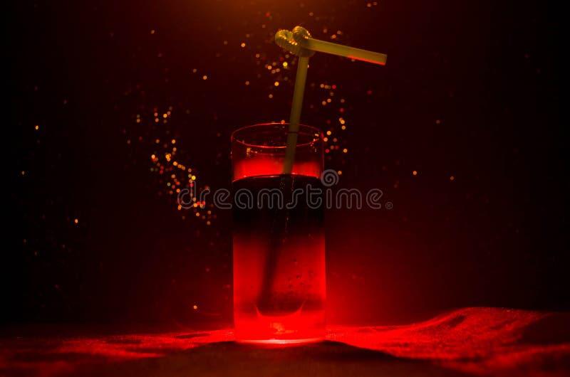 Exponeringsglas av den röda alkoholiserade coctailen på mörk bakgrund med rök och panelljuset Varm coctail för brand klubbabegrep arkivbilder