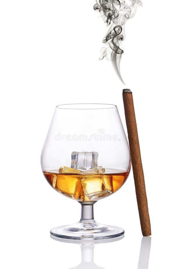 Exponeringsglas av den starka alkoholdrycken kväv whisky med iskuben och rökacigarren royaltyfria bilder