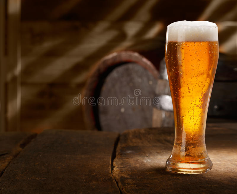 Exponeringsglas av foamy öl på en bordlägga i en ölkällare arkivbild