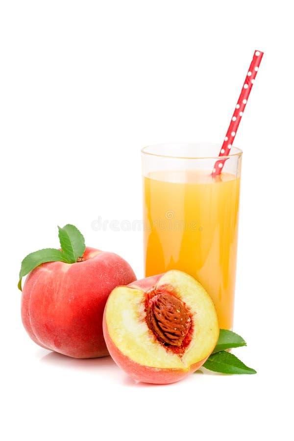 Exponeringsglas av fruktfruktsaft med sugrör och klippta persikor som isoleras på vit bakgrund royaltyfri bild