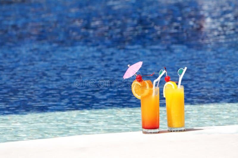 Exponeringsglas av fruktfruktsaft på bakgrund för blått vatten arkivbild