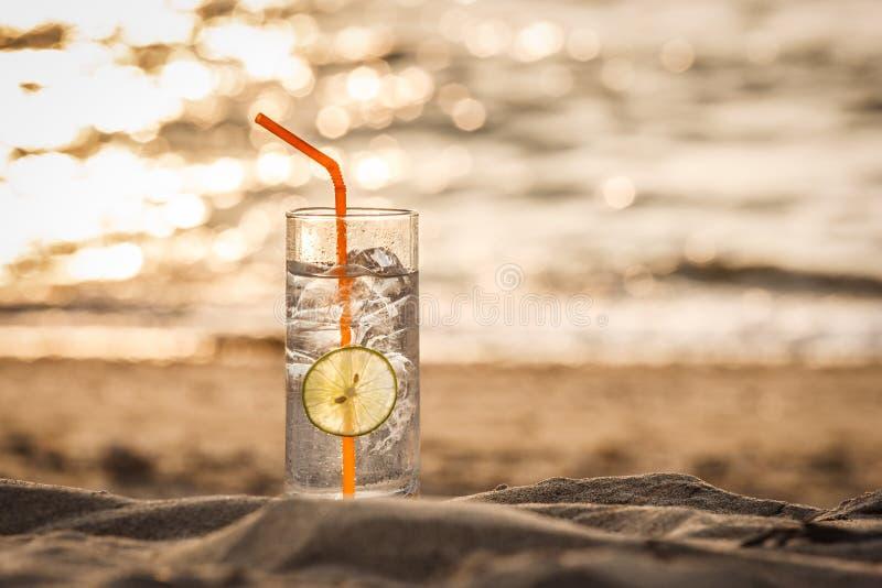 Exponeringsglas av Gin Tonic med sugrör- och limefruktskivan på stranden, på solnedgången Long Beach Ko Lanta, Thailand royaltyfri bild