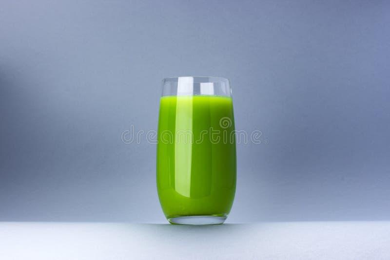 Exponeringsglas av grön fruktsaft som isoleras på vit bakgrund med kopieringsutrymme för text, nytt äpple och sellericoctail arkivfoton