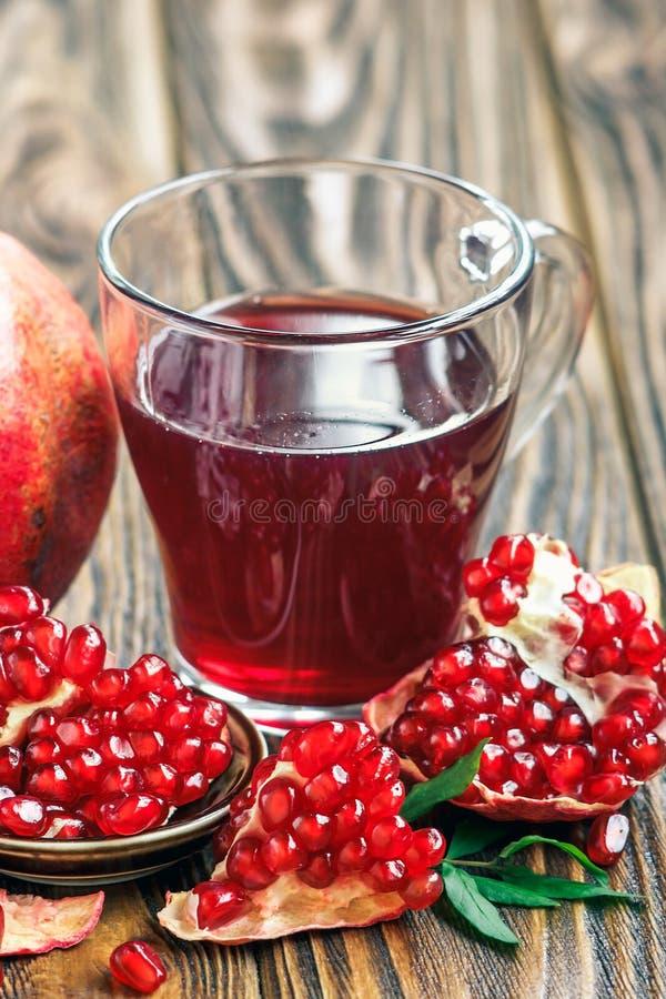 Exponeringsglas av granatäpplefruktsaft med mogen ny punicagranatum bär frukt med sidor på trätabellen royaltyfria bilder
