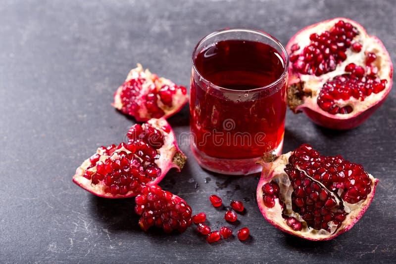 Exponeringsglas av granatäpplefruktsaft med nya frukter royaltyfria foton