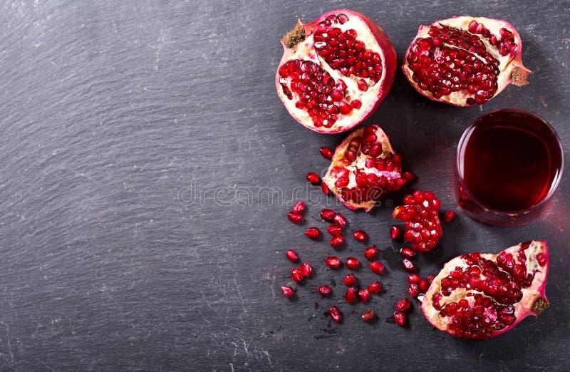 Exponeringsglas av granatäpplefruktsaft med nya frukter royaltyfri foto