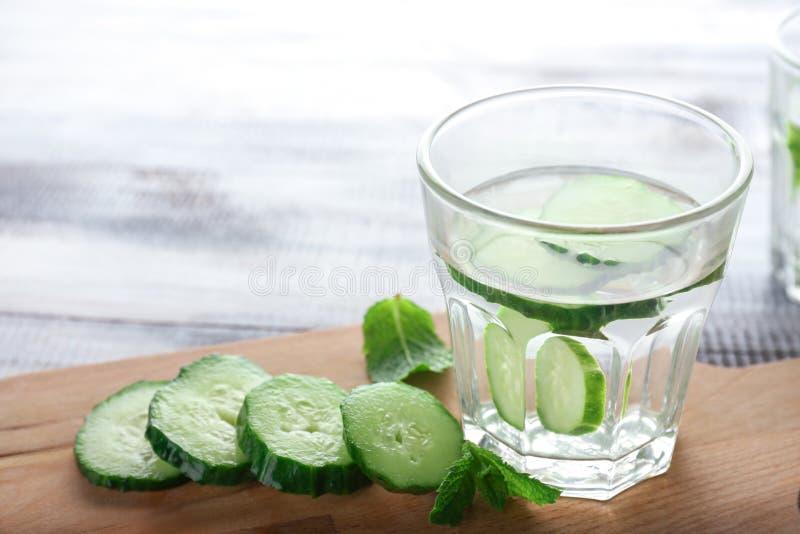 Exponeringsglas av gurka ingett vatten på träbräde royaltyfria foton