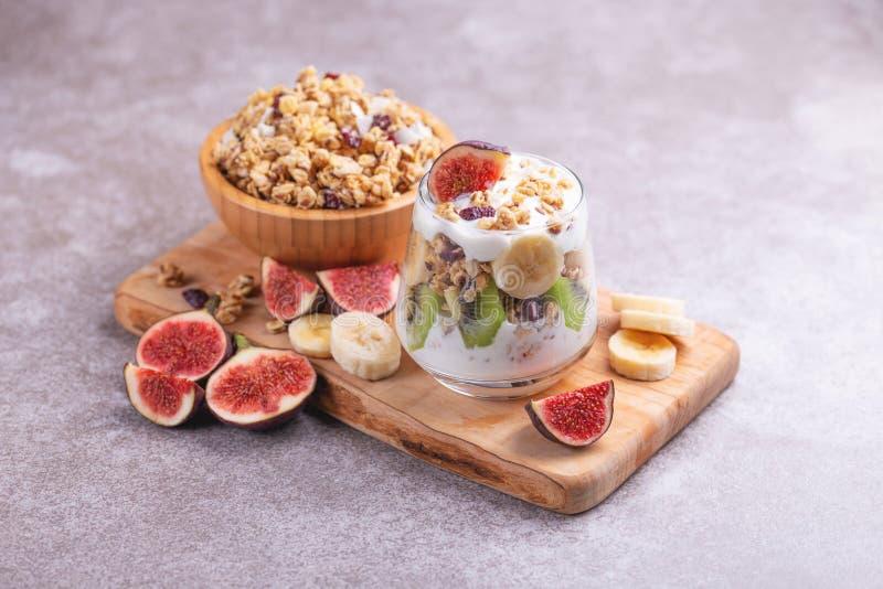 Exponeringsglas av hemlagad granola med yoghurt och nya bananer och fikonträd på grå färger kritiserar bakgrund arkivbild