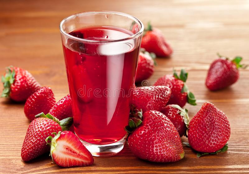 Exponeringsglas av jordgubbefruktsaft och jordgubbar på trätabellen fotografering för bildbyråer