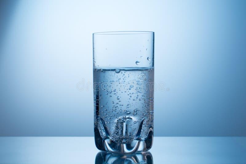 Exponeringsglas av kall ny mousserande mineralvatten på blå grandient bakgrund royaltyfri foto
