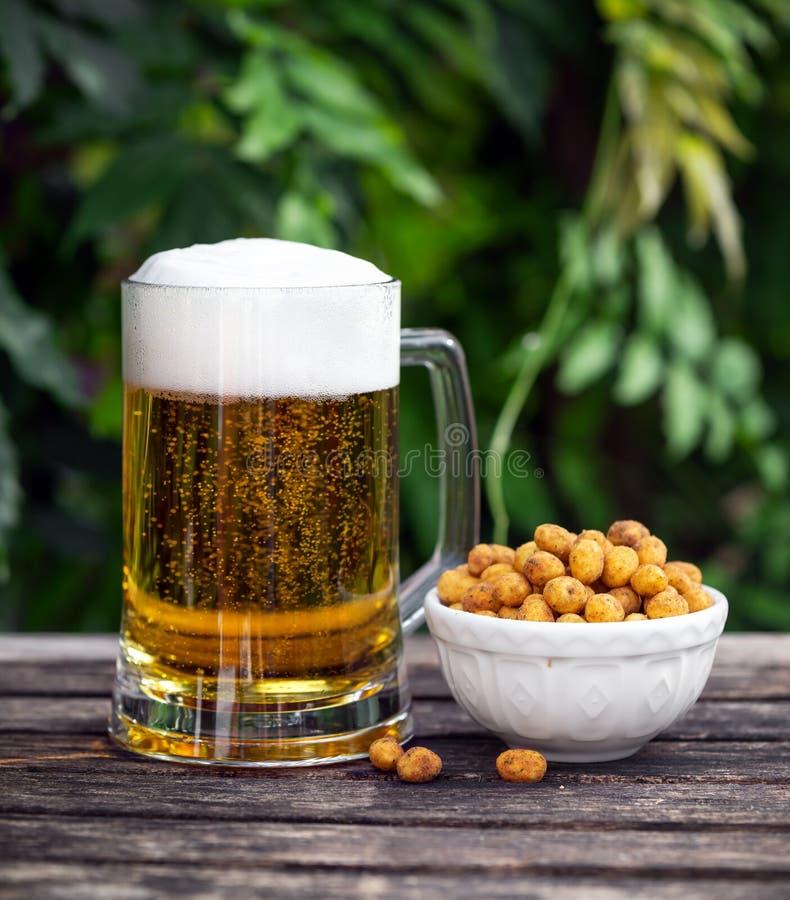 Exponeringsglas av kallt öl med mellanmålet, bestrukna jordnötter på trätabellen i trädgård arkivfoto