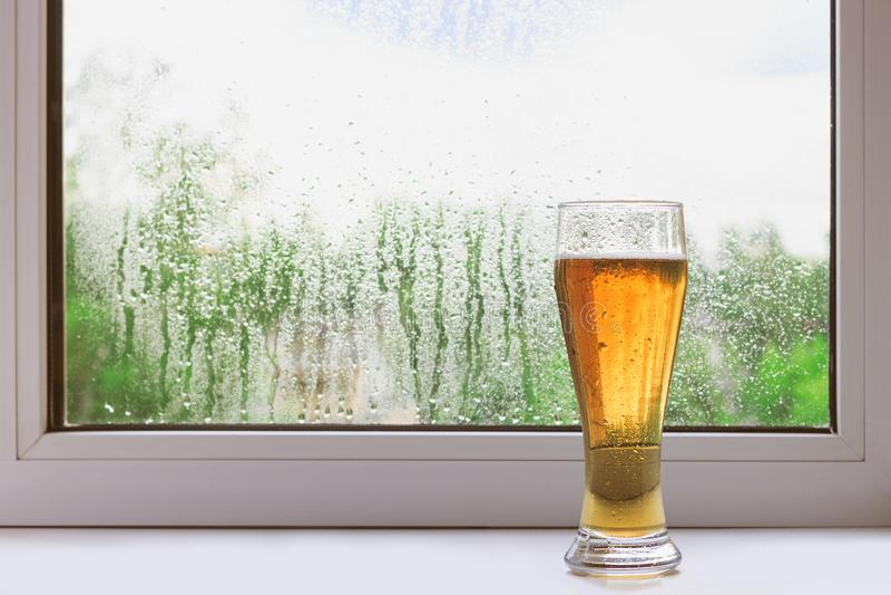 Exponeringsglas av kallt öl på fönsterbrädan på en regnig sommardag Sikten från fönstret Regndroppar på exponeringsglas fotografering för bildbyråer