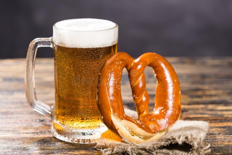 Exponeringsglas av kallt blekt öl med en kringla på en lantlig trätabell arkivfoto