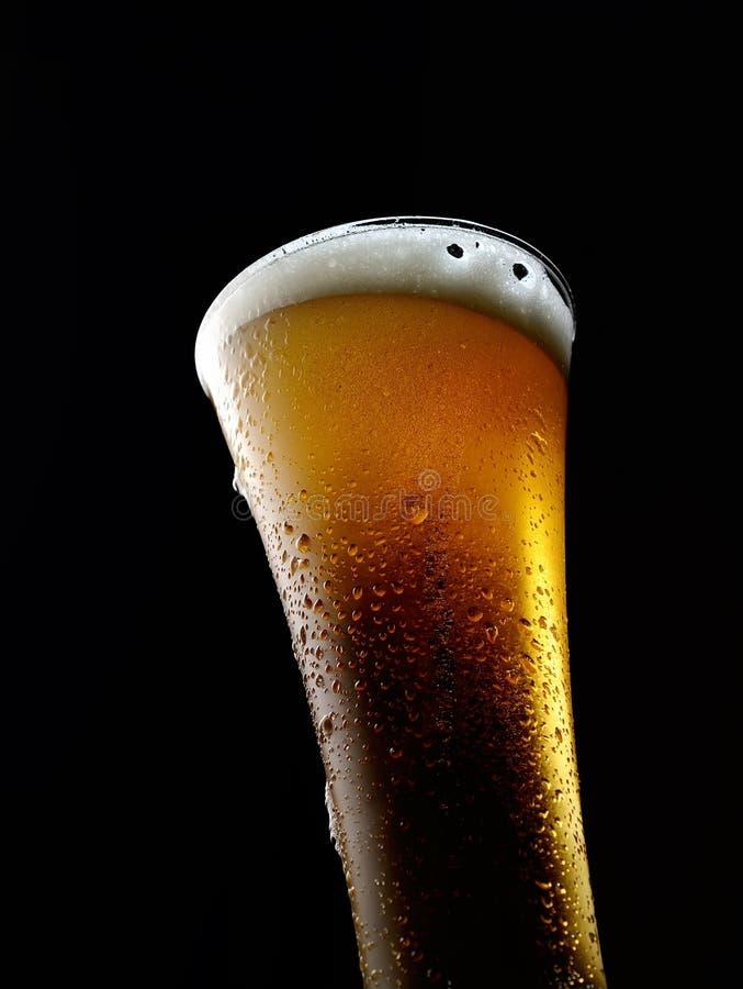 Exponeringsglas av kallt skummande öl på en svart bakgrund arkivbild