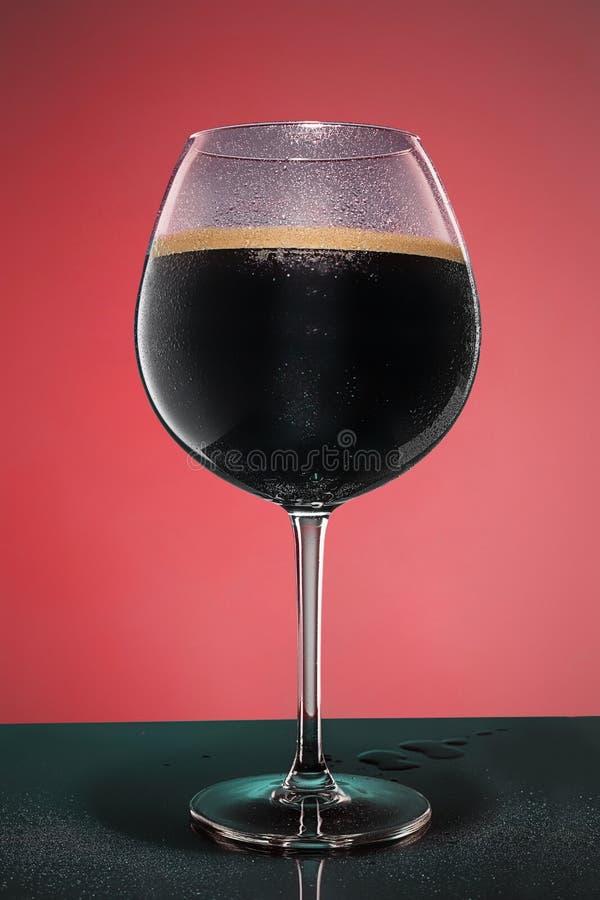 Exponeringsglas av kallt skummigt mörkt öl på en gammal trätabell royaltyfri bild