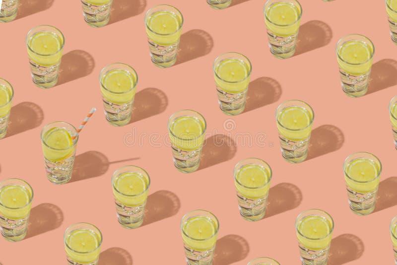 Exponeringsglas av kallt vatten med is och citronen Upprepa modellen på en rosa bakgrund royaltyfria foton
