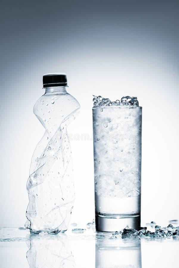 Exponeringsglas av kallt vatten med is och den skrynkliga plast- flaskan på reflekterande yttersida royaltyfri fotografi